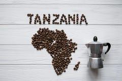 Mapa de la Tanzania hecha de layin asado de los granos de café en el fondo texturizado de madera blanco con el fabricante de café Foto de archivo libre de regalías