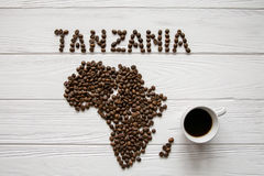 Mapa de la Tanzania hecha de layin asado de los granos de café en el fondo texturizado de madera blanco con la taza de café foto de archivo libre de regalías