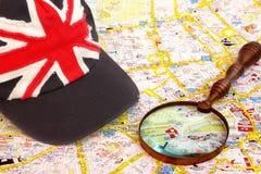 Mapa de Londres, de vidro da lente de aumento e de tampão com bandeira britânica Imagem de Stock