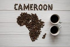 Mapa del Camerún hecho de layin asado de los granos de café en el fondo texturizado de madera blanco con dos tazas de café Foto de archivo libre de regalías