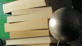 Mapa del globo que da vuelta con una pila de libros almacen de metraje de vídeo
