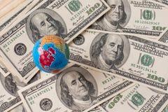 Mapa del globo sobre muchos billetes de banco americanos del dólar fotografía de archivo