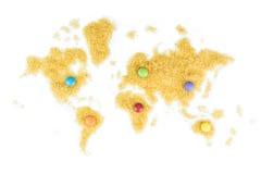 Mapa del mundo hecho del azúcar de caña con los caramelos de chocolate multicolores Imagenes de archivo