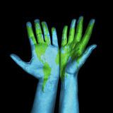 Mapa del mundo pintado en las manos humanas Fotos de archivo libres de regalías