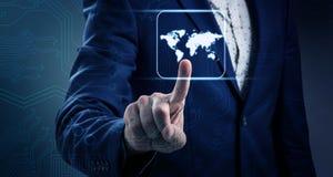 Mapa del mundo que brilla intensamente de los tactos de la mano del ` s del hombre de negocios Fotos de archivo