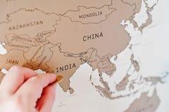 Mapa del viaje del rasguño del mundo Mano del borrado la India del hombre con el co imagen de archivo libre de regalías
