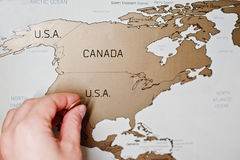 Mapa del viaje del rasguño del mundo Mano del borrado los E.E.U.U. del hombre con la moneda fotografía de archivo