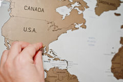 Mapa del viaje del rasguño del mundo Mano del borrado los E.E.U.U. del hombre con la moneda fotografía de archivo libre de regalías