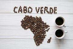 Mapa do Cabo Verde feito dos feijões de café roasted que colocam no fundo textured de madeira branco com duas xícaras de café Imagens de Stock Royalty Free