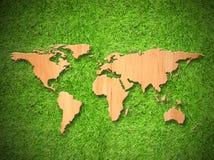 Mapa do mundo de madeira na grama verde Fotos de Stock Royalty Free