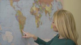 Mapa do mundo tocante do dedo da mulher bonita na parede e no sonho sobre a viagem filme