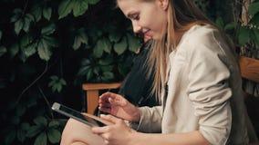 Mapa fêmea novo da leitura do turista no café usando a tabuleta e o telefone para tomar os sentidos, perdidos em uma cidade grand video estoque