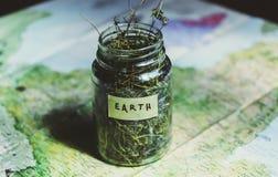 Mapa kontynenty i szklany słój z dzikimi kwiatami i trawą, jak symbol surowy Ziemska planeta Zdjęcie Royalty Free