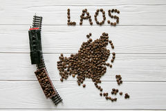 Mapa Laos robić piec kawowe fasole kłaść na białym drewnianym textured tle z zabawka pociągiem Obrazy Stock