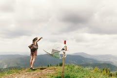 Mapa perdidoso del viajero de la mujer elegante del inconformista encima de las montañas Fotografía de archivo libre de regalías