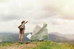 Mapa perdidoso del viajero de la mujer elegante del inconformista encima de las montañas Imagen de archivo