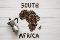 Mapa Południowa Afryka robić piec kawowe fasole kłaść na białym drewnianym textured tle z kawowym producentem Zdjęcia Stock