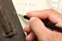 Mapa y lápiz en mano del hombre Fotografía de archivo libre de regalías