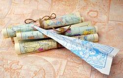 Mapas rolados velhos e avião de papel Fotografia de Stock Royalty Free