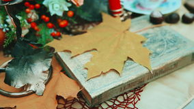Maple autumn leaf on a book. The book is on the table. Autumn, yellow leaves. A park. stock footage