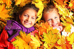 Maple girls. Portrait of two cute girls sisters lying on the leaves at the autumn park Stock Photos