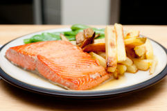 Maple glazed salmon fillet, french fries and snap peas Stock Images
