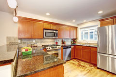 Maple kitchen cabinets with steel appliances and granite tops Royalty Free Stock Images