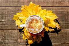 Maple Leaf Latte Art on Arranged Leaves and Wood Surface Royalty Free Stock Photography