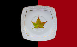 Maple leaf in a white ceramic saucer Stock Photo