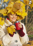 Maple leaves and smiling  girl. The girl in the autumn wood look at the  mug in hands Royalty Free Stock Images