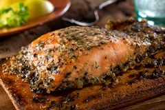 Maple Pepper Cedar Planked Salmon. A serving of delicious maple and smoked pepper cedar planked salmon stock photo