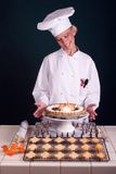 Maple Pumpkin Pie. Passive posed uniformed female Pastry Chef smiling at a finished maple leafed pumpkin pie Royalty Free Stock Photography