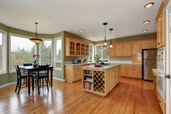 Maple storage combination and large island in the kitchen room Stock Image