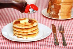 Maple Syrup being poured on a stack of pancakes Royalty Free Stock Images