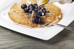 Maple Syrup with Blueberry Pancakes. Pure maple syrup being poured onto freshly made pancakes with blueberries on top royalty free stock photos
