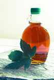 Maple syrup in a bottle with maple leaf Royalty Free Stock Photos