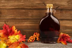 Maple syrup bottle on a wooden plank background. Maple leaves in decoration. Copy space for your text stock photography