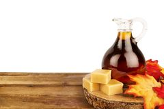 Maple syrup bottle on a wooden plank, isolated on white. Maple syrup bottle on a wooden plank, isolated on white background. Copy space for your text stock photos