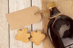 Maple syrup bottle on a wooden plank. Copy space for your text. stock photo