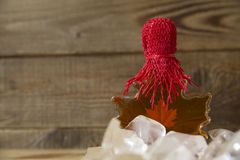 Maple syrup in a glass bottle in the form of a maple leaf on ice  on a wooden rustic background. Maple syrup in a glass bottle in the form of a maple leaf on ice royalty free stock images