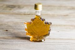 Maple syrup in glass bottle isolated on wooden background stock photos