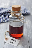 Maple syrup. In glass bottle on a wooden background Royalty Free Stock Photography