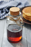 Maple syrup. In glass bottle on a wooden background Royalty Free Stock Photos