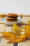 Maple syrup honey and yellow maple leaf and biscuits. On wooden table, autumn canadian sweets Stock Photo