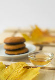 Maple syrup honey and yellow maple leaf and biscuits. On wooden table, autumn canadian sweets Stock Photography