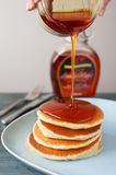 Maple syrup pouring onto pancakes. Stock Photos