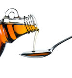 Maple syrup pouring on spoon. On white background Stock Photo