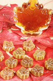 Maple taste. Maple syrup and maple syrup candies on a bed of maple leaves Stock Photos