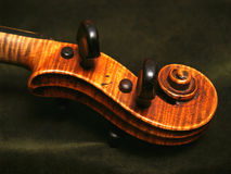 Antique Maple Violin Scroll on Olive Green Velvet Stock Image