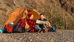 Mappa d'esplorazione delle coppie caucasiche dei pantaloni a vita bassa nella montagna durante il giorno soleggiato mentre stanno fotografia stock